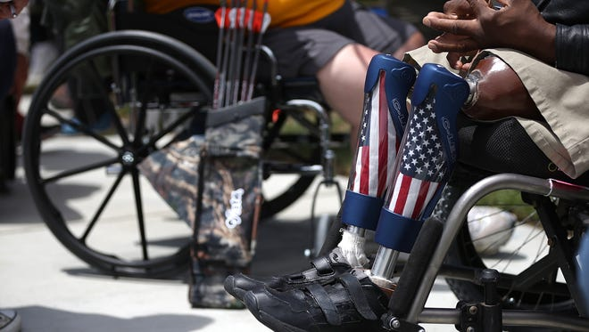 A veteran with prosthetic legs watches an archery competition at the inaugural Valor Games Far West in Foster City, Calif., June 11.  Dozens of disabled and wounded military veterans participated in the games. About 1.1 million Americans care for ailing or disabled veterans of the Iraq and Afghanistan Wars.