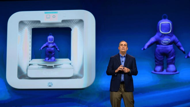 Intel  CEO Brian Krzanich delivers a keynote address in front of an image of a 3D Systems Cube 3-D printer at the 2014 International CES at The Venetian Las Vegas on Jan. 6, 2014.