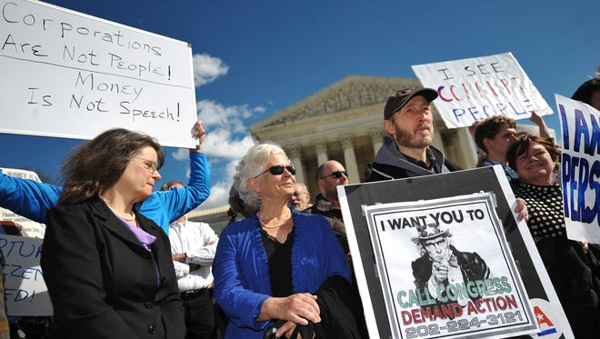 """People outside of the Supreme Court in February 2012 call for a reversal of the """"Citizens United"""" decision in Washington, D.C."""