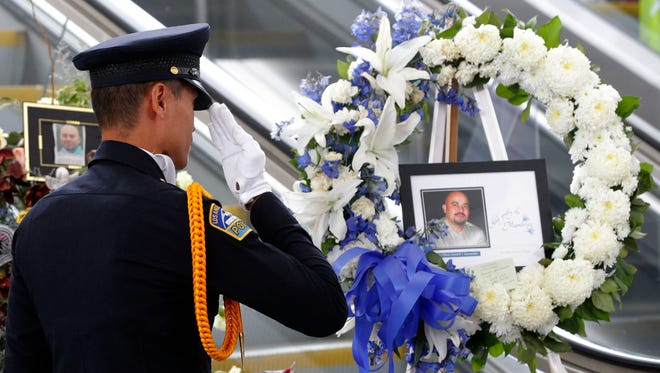 TSA officer Fritz Corros salutes at Los Angeles International Airport, during a moment of silence Friday to honor the Transportation Security Administration officer Gerardo Hernandez, killed by a gunman at the airport a week ago.