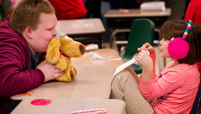 Evans Elementary School third-graders Troy Mominee Jr., left, and LaRissa Hall play with their new stuffed animal gifts in Rachel Davidson's class Friday afternoon. The gifts were the result of a collaboration between Davidson and  Thompkins Middle School students and teachers.
