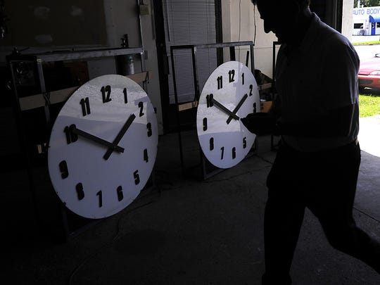 Sam Medawar puts the finishing touches on repaired clock tower faces at his workshop in Lansing Tuesday July 21, 2015. The clock faces will be remounted in the Haslett Commerce Center Tower.