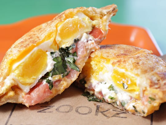 Poached egg, bacon, Cheddar cheese, cream cheese, tomato and fresh basil sandwich from Zookz Sandwiches.