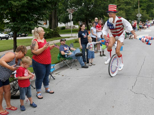 A man dressed as Uncle Sam rides down the line of spectators