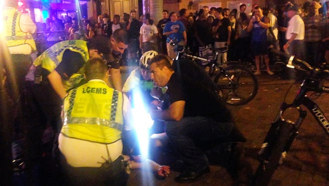 Emergency medical workers and police work next to an injured person at the scene of a shooting on Oct. 17, 2015, at ZombiCon in Fort Myers, Fla.