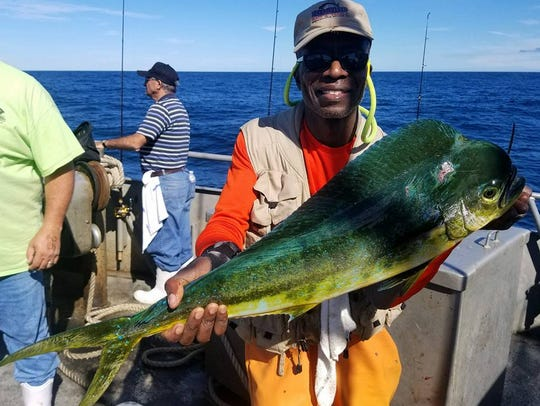 An angler holds a mahi-mahi landed on the 125-foot