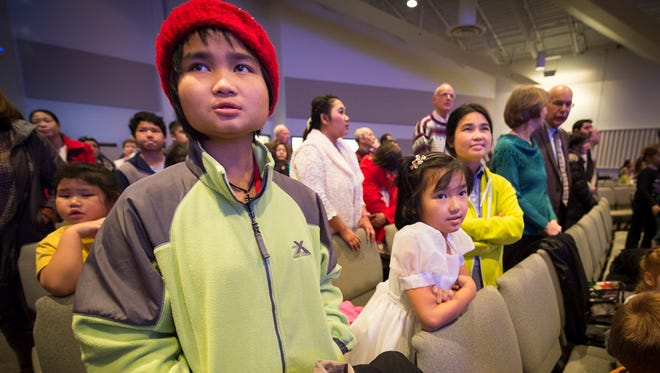"""Easter Day, 15, left, along with her sister, Daily Joy, 9, and her mother, Kaw Paw, join along in the singing """"Joy to the World"""". Volunteers at Faith Missionary Church lead English classes for 350 refugees and immigrants. The end of the semester Christmas party was Tuesday, Dec. 8, 2015."""