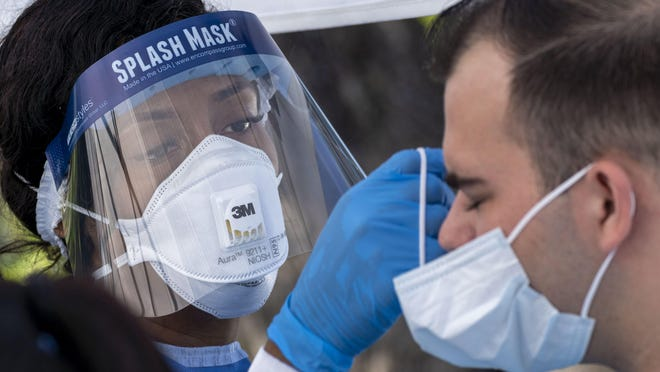 Dr. Oneka Marriott helps with a mask at a drive through station set up to test for COVID-19 in the parking lot of FoundCare, federally qualified health center in West Palm Beach, Florida on March, 16, 2020.