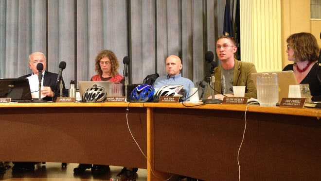 Progressive Burlington City Councilors Rachel Siegel, second from left, Vince Brennan and Max Tracy displayed bicycle helmets Monday night in support of a resolution to add bike lanes and make other changes to North Avenue. Tracy, who introduced the resolution, also wore a bicycle-themed shirt.