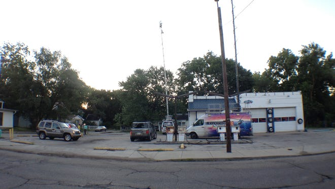 Television news trucks are posted near the scene where IMPD officers shot a suspect early Tuesday morning.