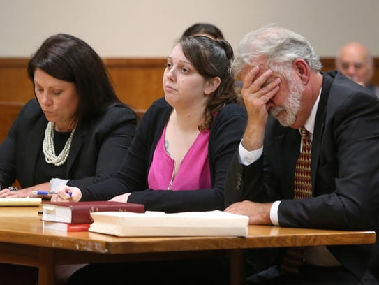 Erica Bell, center, sits flanked by her attorneys Sarah