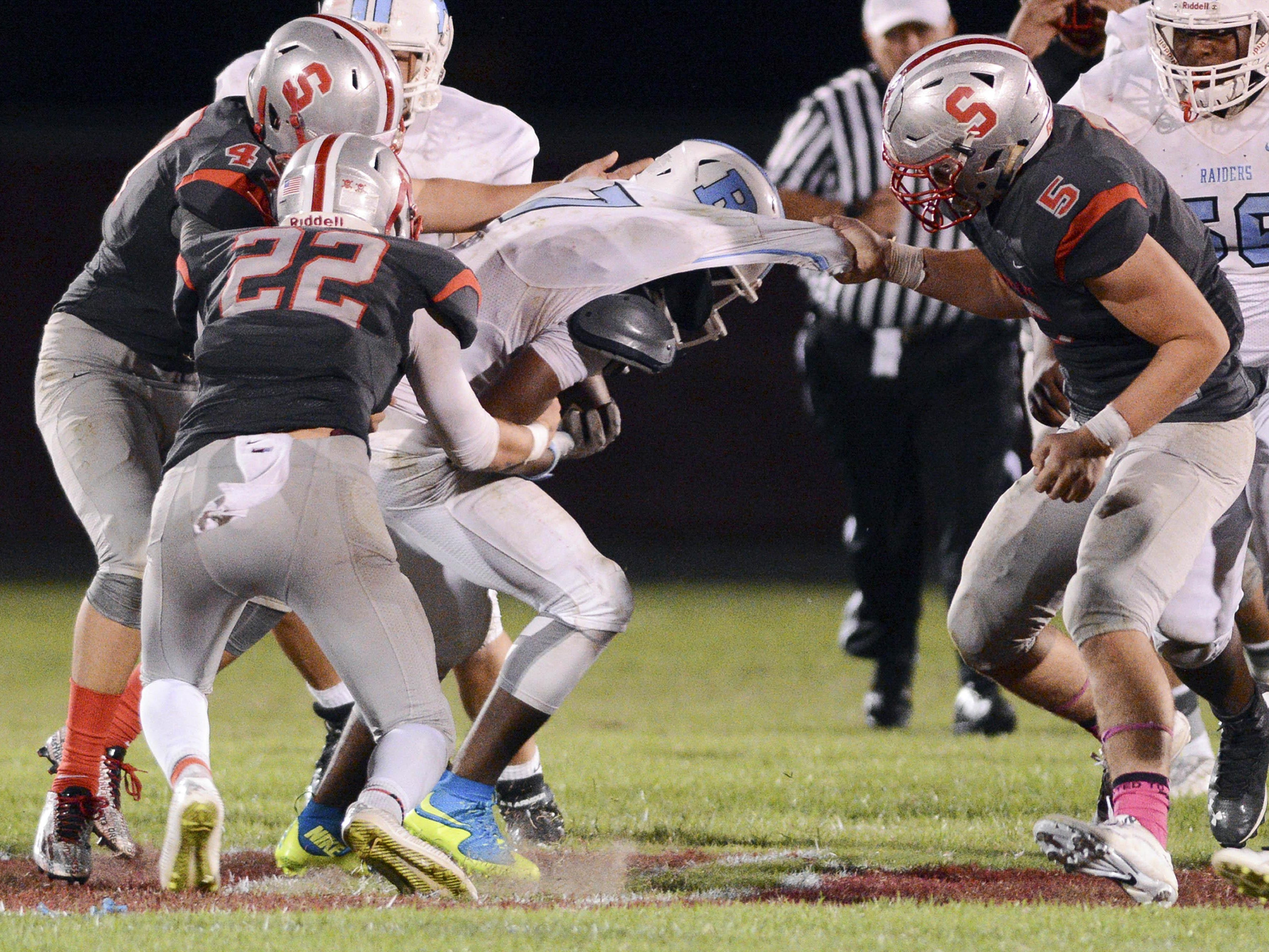 Jalen Mitchell of Rockledge is taken down by Satellite players Andrew Abendroth (47) David Eaton (22) and Kyle Bassagnani (5) during last week's game in Satellite Beach.