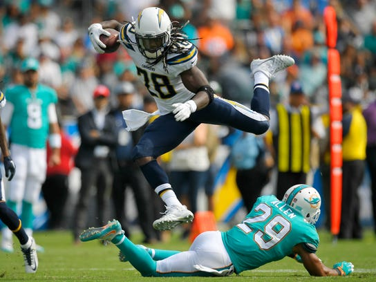 Los Angeles Chargers running back Melvin Gordon (28) leaps over Miami Dolphins defensive back Nate Allen during the second half of an NFL football game Sunday, Sept. 17, 2017, in Carson, Calif. (AP Photo/Mark J. Terrill)