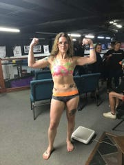 Shamir Peshewa flexes her muscles at weigh-ins before a recent fight.