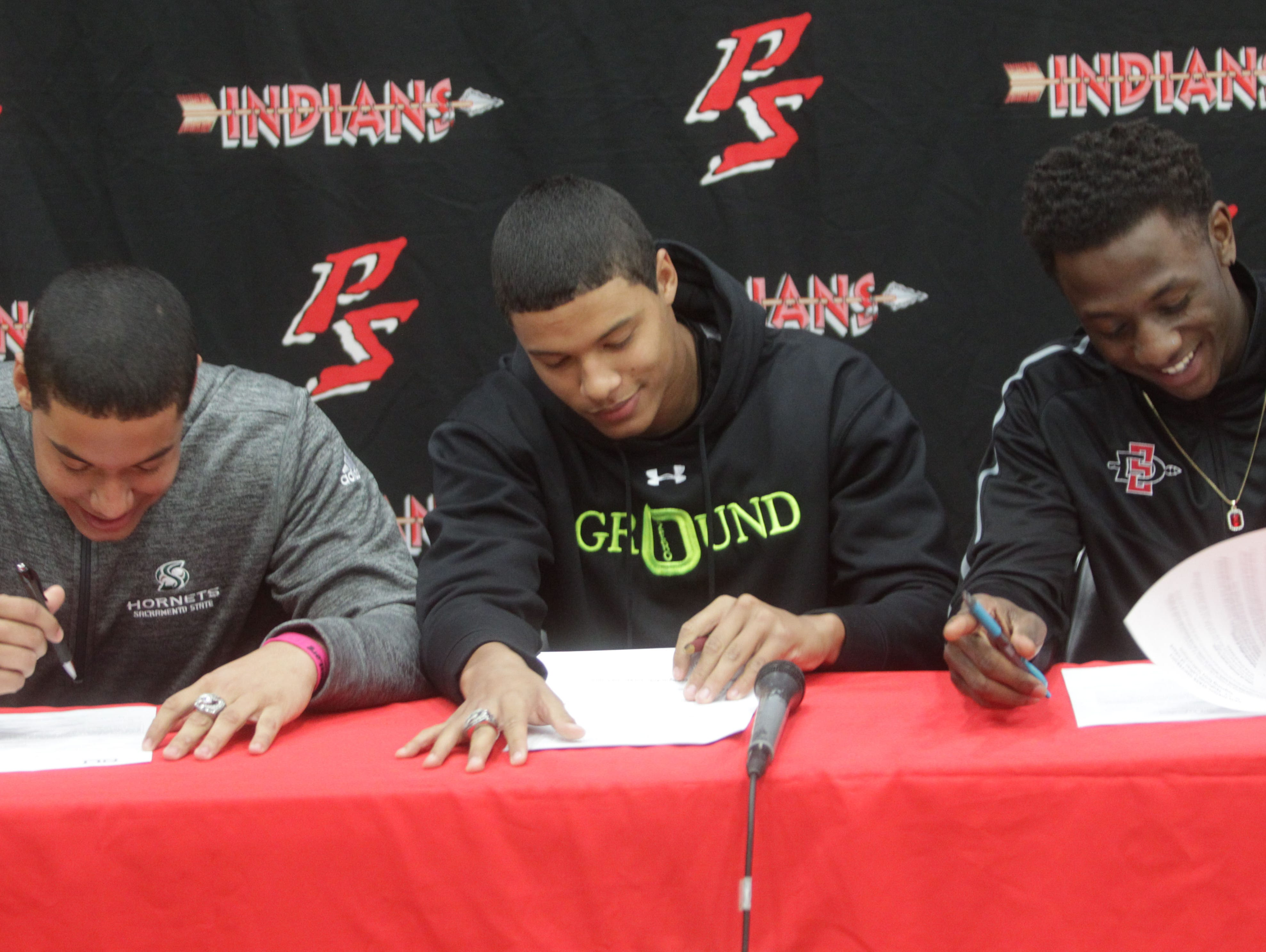 From left, twins, Tyler and Tayler Hawkins and Trenton Thompson, all students of Palm Springs High School sign their letter of intent to attend Universities on football scholarships. Tyler will attend Sacramento State and Tayler and Trenton will attend San Diego State University.