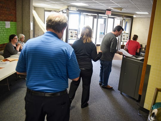 Voters enter their ballots into the counting machine for the Sauk Rapids-Rice School District referendum Tuesday, May 8, at Pleasantview Elementary School.