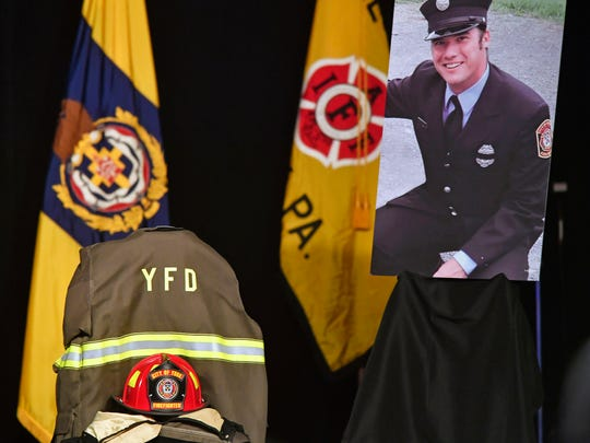 Zachary Anthony's helmet and turnout gear are displayed with his portrait onstage at a public memorial service.