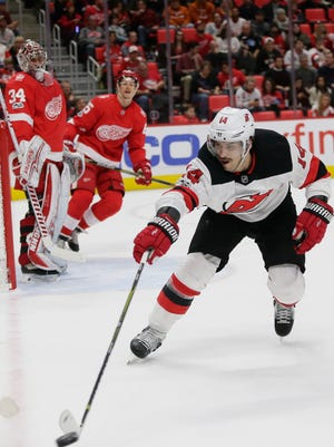 New Jersey Devils center Adam Henrique (14) tries to block a pass against the Detroit Red Wings during the first period of an NHL hockey game Saturday, Nov. 25, 2017, in Detroit. (AP Photo/Duane Burleson)
