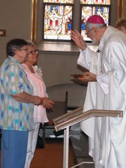 Bishop Sklba blesses the two jubilarians who brought