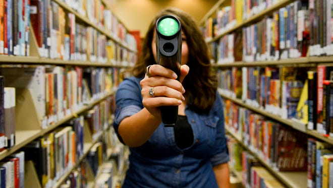 """Eli R. Klein, the online content, social media & PR coordinator for CADL, holds a a thermal leak detector in the downtown library Friday, Sept. 9, 2016. Capital Area District Libraries recently launched the """"Library of Things"""" which allows for the check out of different technology and other devices. Items include a telescope, sewing machine, metal detector, bird watching kit, Raspberry Pi computer kit and more."""