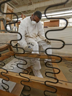 Inmate Jamonn Grier, removes old varnish from a classic antique couch that he was refinishing in the wood working shop at James T. Vaughn prison in Smyrna.