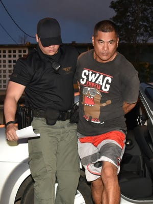 Anthony Pangelinan Santos is brought to the Guam Police Department Hagatna precinct by Criminal Justice Strike Force Officer A.P. Doyle on Thursday, May 28.