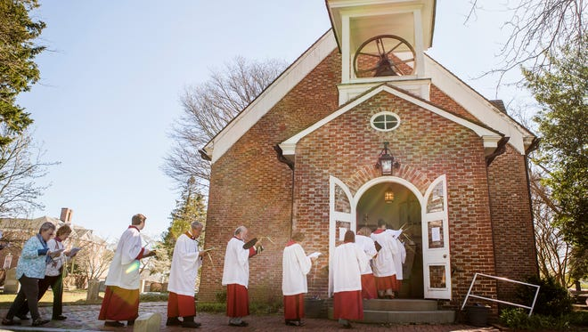 Members of the Christ Church congregation process to the church from the corner of South State and East Water Streets as they celebrate Palm Sunday in Dover on Sunday morning.
