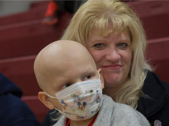 Trevor Kwatkoski, a 5-year-old battling bone cancer,  sits with his mother, Jill, as they wait for the start of the boys basketball game to start at Central Regional Thursday night.