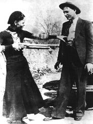 Bonnie Parker aims a gun on her partner in crime, Clyde
