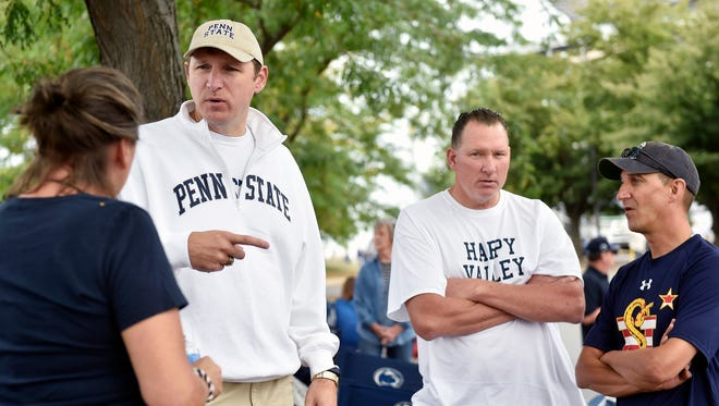 From left, Patty Stephens of Washington, DC.; Keith Karpinski of Detroit; Bob Mroskow of Middleville, Ohio; and Stephens' husband Mark catch up before an NCAA Division I college football game Saturday, Sept. 17, 2016, at Penn State. The university plans to honor former head football coach Joe Paterno and his players' legacies in a celebration of the 50th anniversary of his first game as coach. Karpinski and Mroskow played for Penn State in 1984-1988.