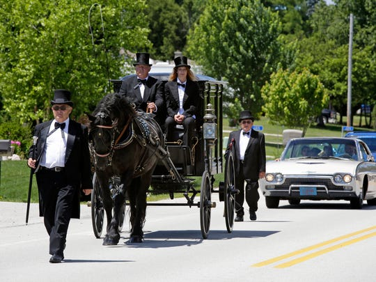 Randy Raab leads the horse-drawn hearse procession for the funeral of Arnold Raab, of Cascade, along Superior Avenue at Greenlawn Memorial Park Friday in Kohler.  Dennis Raab, of Auburndale, and granddaughter Brittany Raab control the hearse, while Allen Raab, of Sheboygan, follows behind.