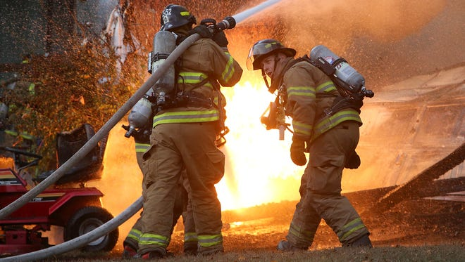 Firefighters battle a garage fire near the corner of Hancock Cove and North Hampton Lane in North Jackson, on Monday, Nov. 2, 2015.
