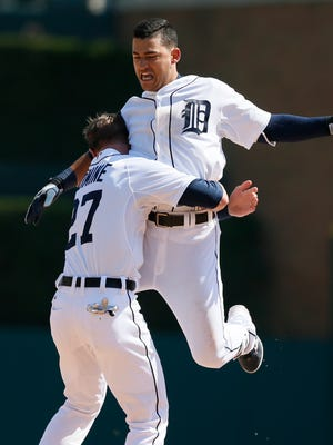 Detroit Tigers shortstop Jose Iglesias jumps into he arms of Andrew Romine after Iglesias hit the game-winning single in the bottom of the ninth inning to beat the Chicago White Sox 2-1 on April 17, 2015 in Detroit.