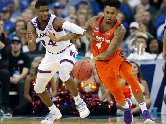 Kansas' Malik Newman (14) and Clemson's Shelton Mitchell chase a loose ball during the second half of a regional semifinal game in the NCAA men's college basketball tournament Friday, March 23, 2018, in Omaha, Neb. (AP Photo/Charlie Neibergall)