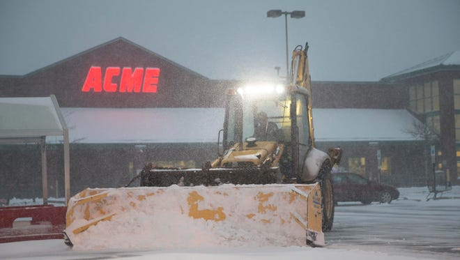 Contractor keeps the parking lot at the Acme in Barnegat clear as storm rages on.