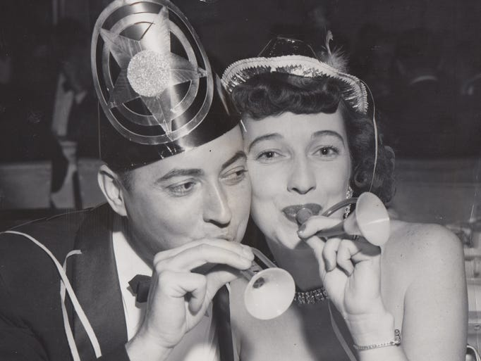 With paper hats and confetti, Mrs. and Mrs. John Baker welcome the 1953 at the Indianapolis Athletic Club New Year's Eve party.