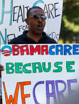 Willie White of Albany, N.Y., holds a sign during a 2012 rally supporting President Obama's health care overhaul.