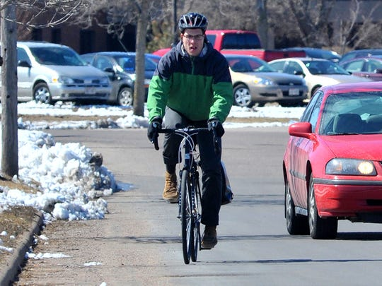 Cyclists should bike about three feet from the curb, and cars should give them three feet when passing. Aaron Ruff, 26, of Wausau, peddles his bicycle from work Friday afternoon, March 27, 2015, along Lake View Drive in Wausau.