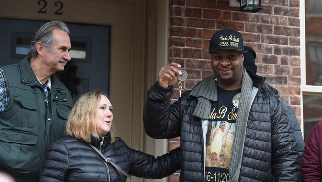 Keith Smith, right, waves the keys to his family's new home in the City of Newburgh after the dedication ceremony. The house, rehabbed by Habitat for Humanity, used the wood from the 2015 Rockefeller Center Christmas Tree. Albert Asendorf, left, and his partner Nancy Puchalski, center, own the property in Gardiner where that tree grew.
