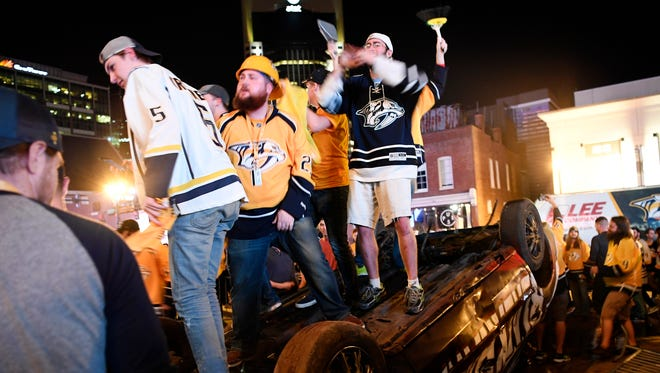 Fans jump on top of the overturned demolition car after the Predators beat the Blackhawks 4-1 to sweep the first-round NHL playoff series at the Bridgestone Arena, Thursday, April 20, 2017, in Nashville, Tenn.