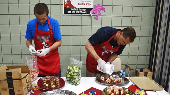Michael Wilde, right, chief medical officer with Sanford Health, prepares Sanford shrimp and sea salt shooters with the help of his son, Patrick, at last year's Gourmet Guys event at Active Generations.
