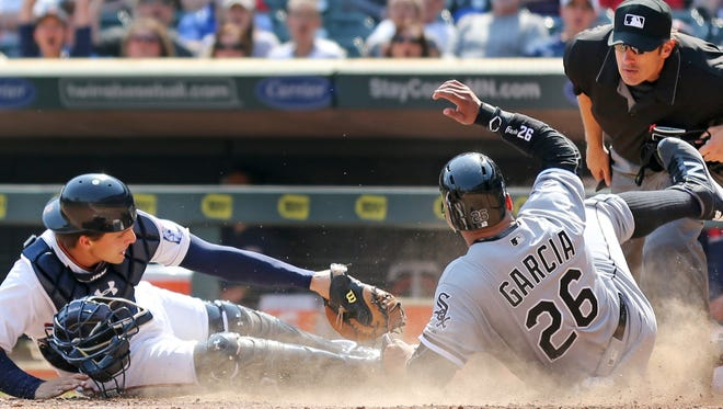 Chicago White Sox's Avisail Garcia (26) is safe at home in the seventh inning as Minnesota Twins catcher John Ryan Murphy (12) was late on the tag during a baseball game at Target Field. Thursday April 14, 2016 in Minneapolis, Minn.  (Jerry Holt Jerry/Star Tribune via AP)