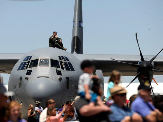 A crew member sits on top of a Dyess C-130J as spectators watch airplanes perform during the Dyess Big Country AirFest on Saturday, May 6, 2017, at the Abilene Regional Airport.