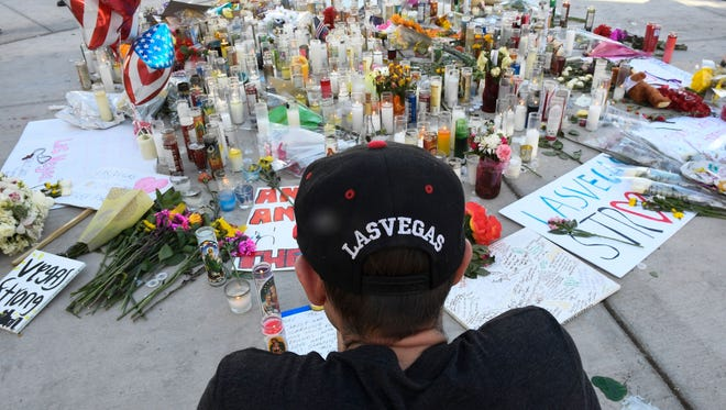 Ken Neyhart of Las Vegas, sits quietly at a makeshift memorial along Las Vegas Blvd. in Las Vegas, Nev. on Oct. 3, 2017.