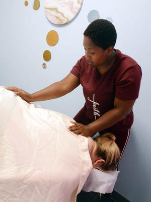 Tiara Waters gives Laura Lyle of Norwich a massage Friday at Flowing Waters Massage at 66 Foundry in downtown Norwich.