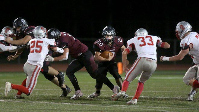 Buhler's Sam Elliott (20) looks for a path to run through during their game against Wellington. Buhler hosts Circle this Friday to start the Class 4A Playoffs.