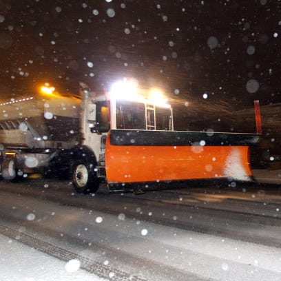 A snow plow travels north on Dixie Highway in Fort