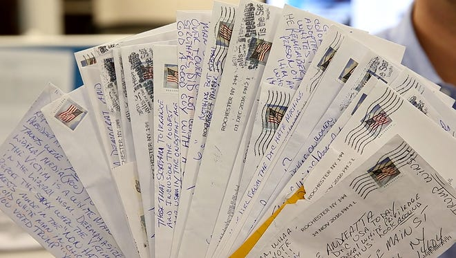 """Columnist David Andreatta holds letters he and others at the """"Democrat and Chronicle"""" have received in recent weeks from an anonymous writer dubbed """"Our Friend."""""""