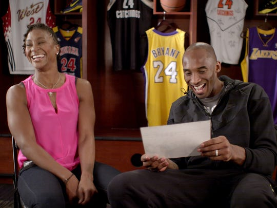 Tamika Catchings and Kobe Bryant laugh at a photo that shows them as children in Italy in 1986, where their fathers were playing basketball.