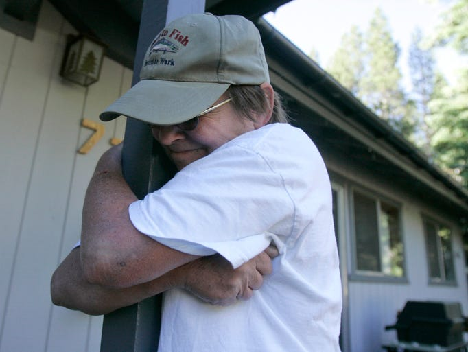 Francine Tanner hugs the beam in the front of her house